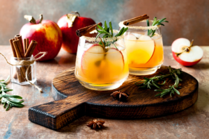 fall cocktails on a wooden board surrounded by apples and cinnamon sticks